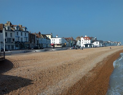 The wide shingle beach and seaside homes.