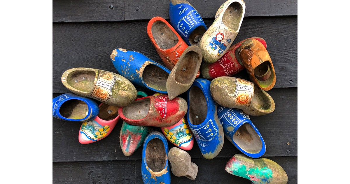 Colorful wooden clogs decorate the side of a house.